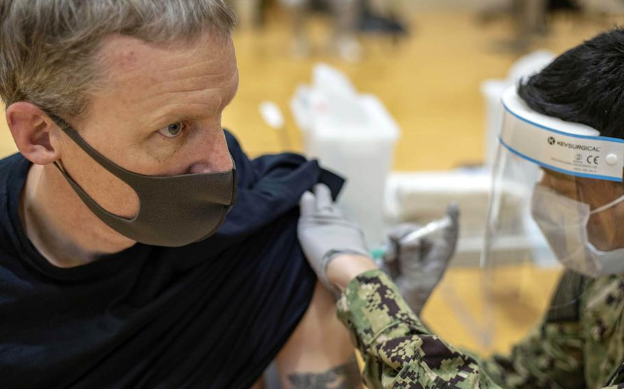Cmdr. Andrew Wiese of the aircraft carrier USS Ronald Reagan receives his first dose of the Moderna COVID-19 vaccine at Yokosuka Naval Base, Japan, Jan. 7, 2021.