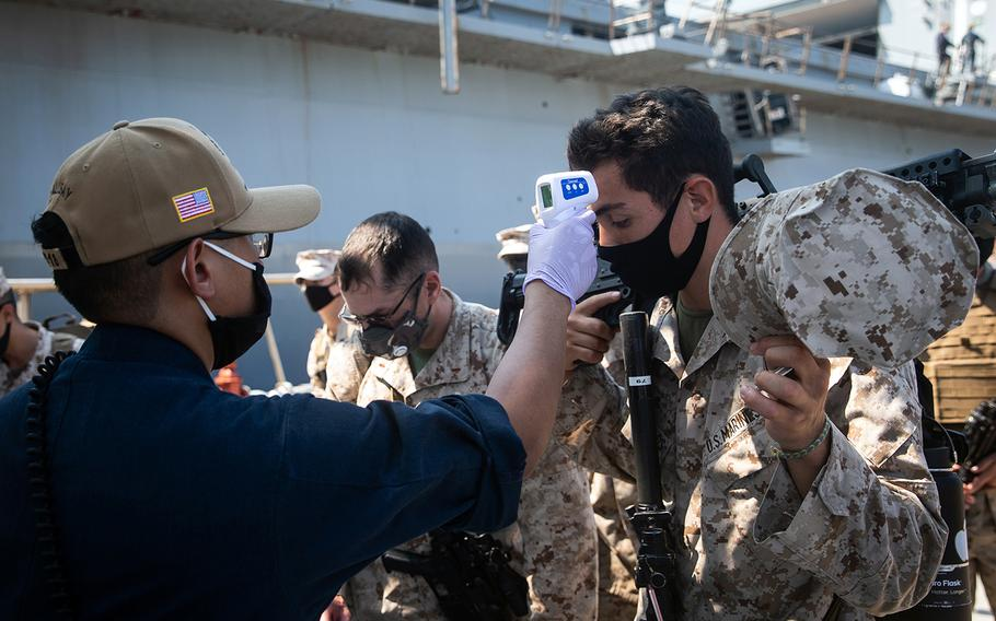 Then-Lance Cpl. Rene PonceAvalos, right, gets his temperature taken as he boards the USS New Orleans at White Beach Naval Base, Okinawa, Aug. 18, 2020.