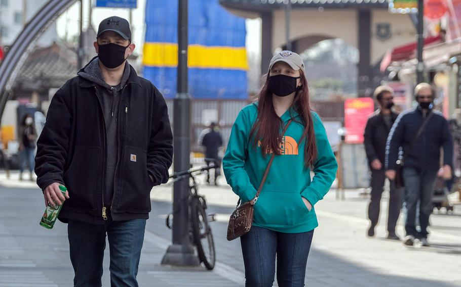 People wear masks while strolling through the Songtan entertainment district outside Osan Air Base, South Korea, Tuesday, March 2, 2021.