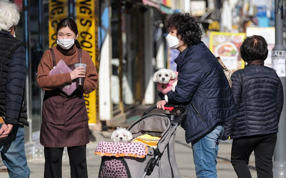 People in masks go out for a walk in Pyeongtaek, South Korea, Tuesday, March 2, 2021.