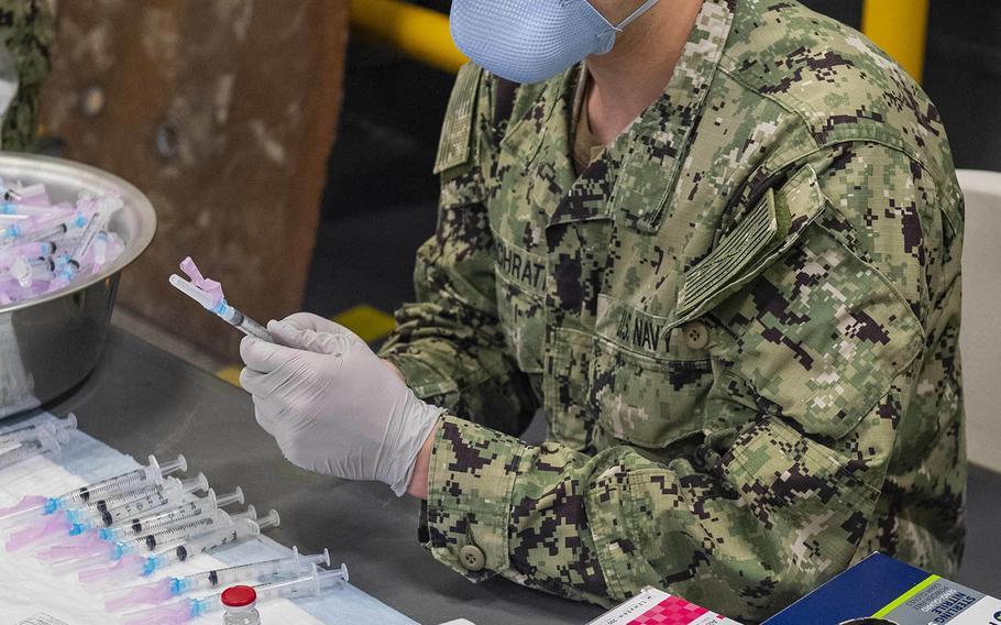 A Navy hospitalman fills syringes with the Moderna COVID-19 vaccine aboard the amphibious assault ship USS America at Sasebo Naval Base, Japan, Feb. 26, 2021.