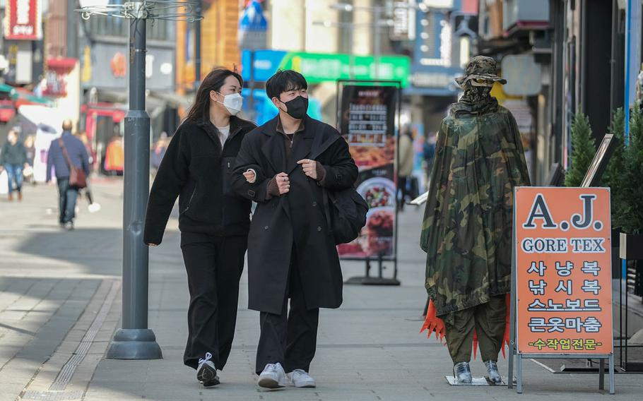 Masked pedestrains check out a shop in Pyeongtaek, South Korea, March 2, 2021.