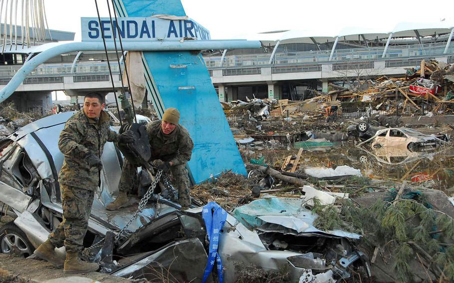 Marines from Combined Arms Training Center, Camp Fuji, remove a smashed vehicle from Sendai Airport following the March 11, 2011, earthquake and tsunami.