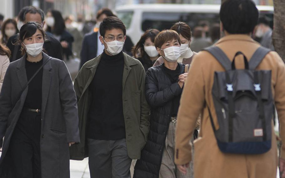 Pedestrians in Ginza, a shopping district in central Tokyo, wear masks as protection against the coronavirus, Tuesday, March 9, 2021.