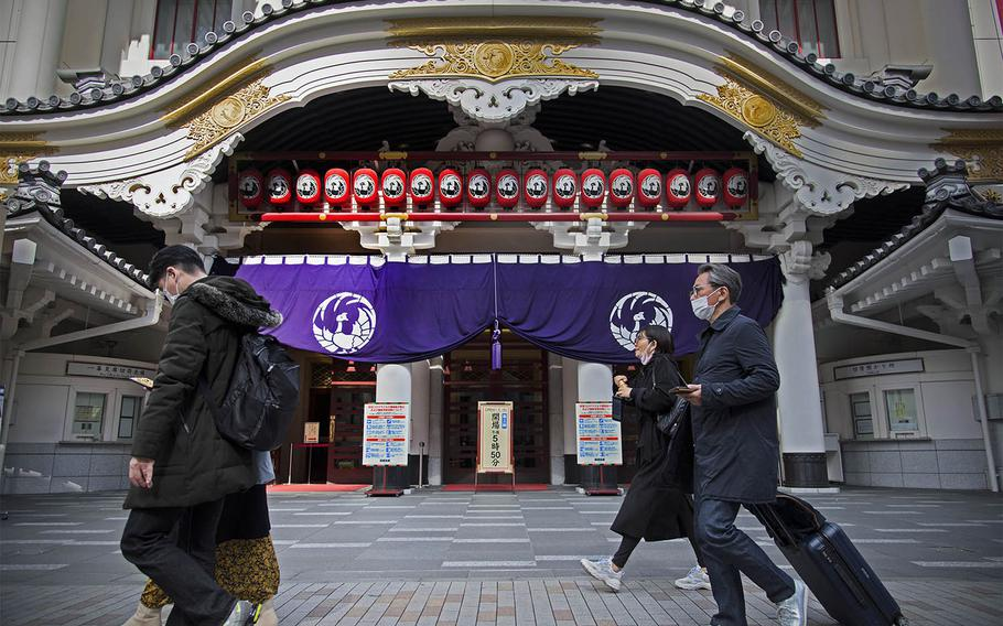 People wear masks as they stroll past the Kabukiza Theatre in Ginza, Tokyo, March 9, 2021.