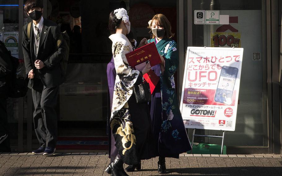 People wear masks outside an arcade in western Tokyo, Friday, March 12, 2021.