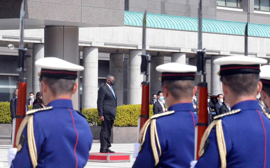 Secretary of Defense Lloyd Austin watches Japanese troops parade in front of the Ministry of Defense in Tokyo, Tuesday, March 16, 2021.