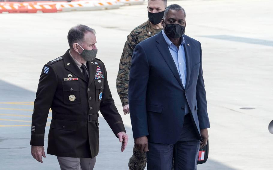 Defense Secretary Lloyd Austin walks with the commander of U.S. Forces Korea, Army Gen. Robert Abrams, after arriving at Osan Air Base, South Korea, Wednesday, March 17, 2021.