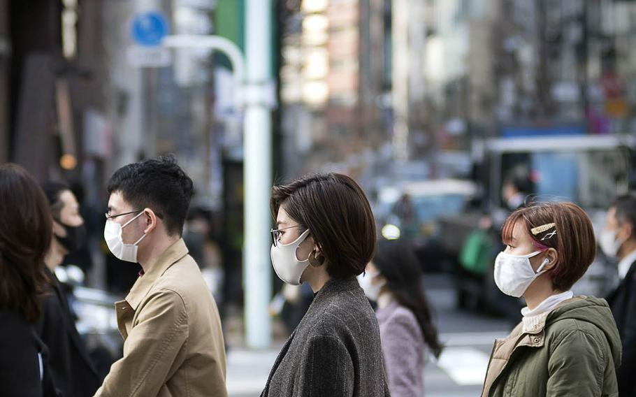 Pedestrians wear masks to guard against the coronavirus in the Ginza district of central Tokyo, March 9, 2021.
