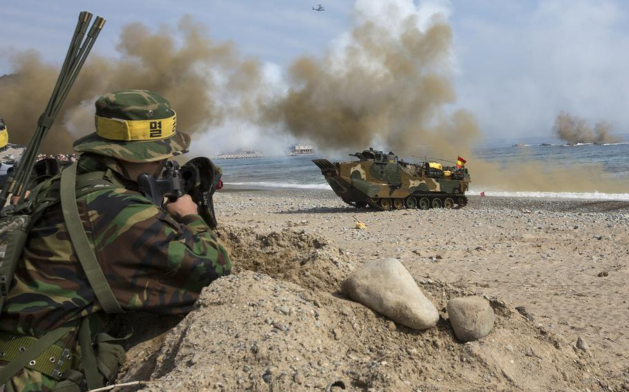 In a March, 2014 photo, Republic of Korea Marines with 7th Marine Regiment, simulated opposition forces, observe as Assault Amphibious Vehicles approach shore during Integrated Amphibious Assault for Ssang Yong 14 at Doksu-ri Beach, Pohang, South Korea. Exercise Ssang Yong is conducted annually in the Republic of Korea (ROK) to enhance interoperability between U.S. and ROK forces.