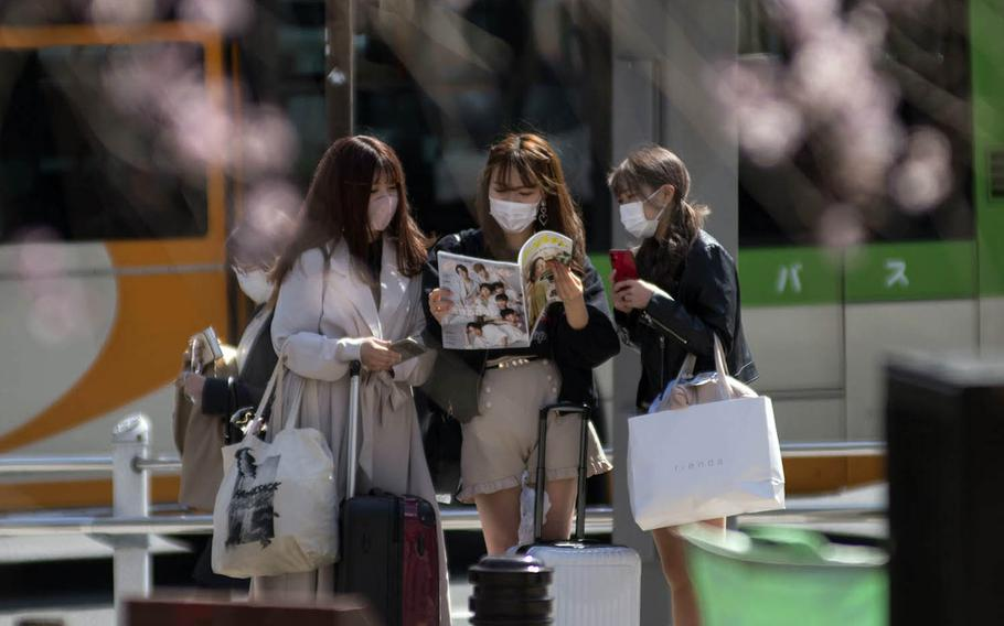 Women wear masks to guard against the coronavirus near Ueno Park in central Tokyo, Wednesday, March 17, 2021.