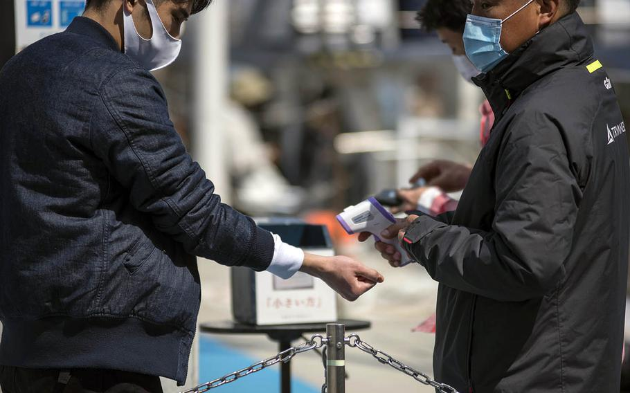 A man wearing a mask as protection against the coronavirus has his tempertature checked, another pandemic precaution, in Yokosuka, Japan, March 19, 2021.