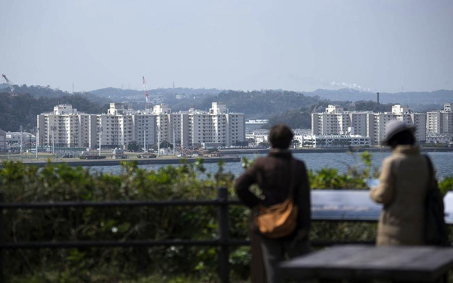 People visiting an observation point check out housing towers and other buildings at Yokosuka Naval Base, Japan, March 19, 2021.