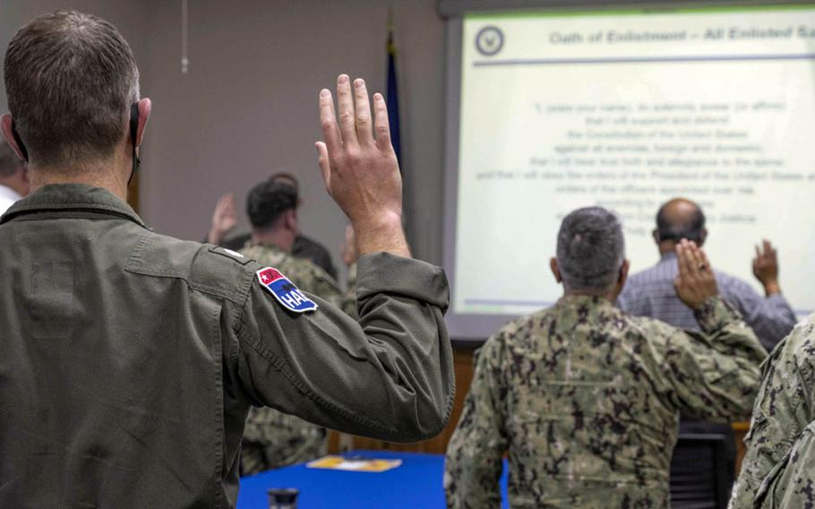 Service members and civilians reaffirm their oaths of office and enlistment during extremism training at Kadena Air Base, Okinawa, March 8, 2021.