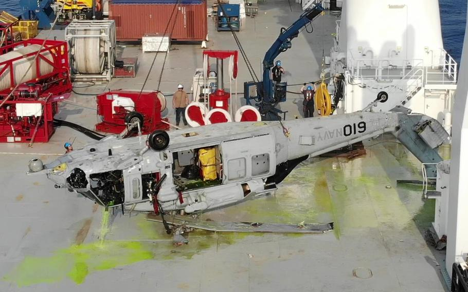 The U.S. Navy Seahawk helicopter lies upside-down on the deck of a salvage ship after being lifted 3.6 miles from the ocean floor near Okinawa on March 18, 2021.