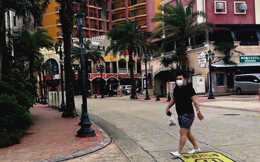 A masked pedestrian strolls through American Village, a popular tourist spot on Okinawa, Tuesday, April 6, 2021.