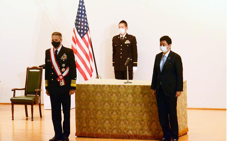 The head of U.S. Indo-Pacific Command, Adm. Philip Davidson, left, receives the Grand Cordon of the Order of the Rising Sun, Japan's third-highest honor, at the Ministry of Defense in Tokyo, Monday, April 12, 2021.