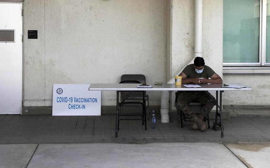 A Navy corpsman takes a break between scheduled coronavirus vaccinations at Naval Hospital Okinawa, Tuesday, April 13, 2021.