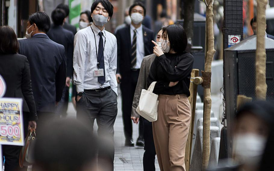 People wearing masks to guard against the coronavirus stroll through Tokyo on April 13, 2021.