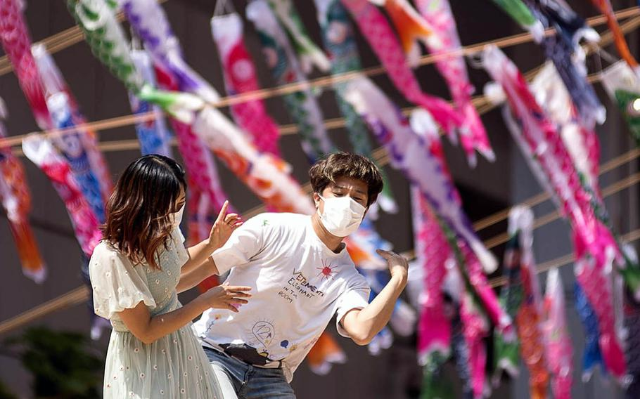 Two people caper beneath Tokyo Tower, decorated with 333 carp-shaped windsock streamers, April 12, 2021.