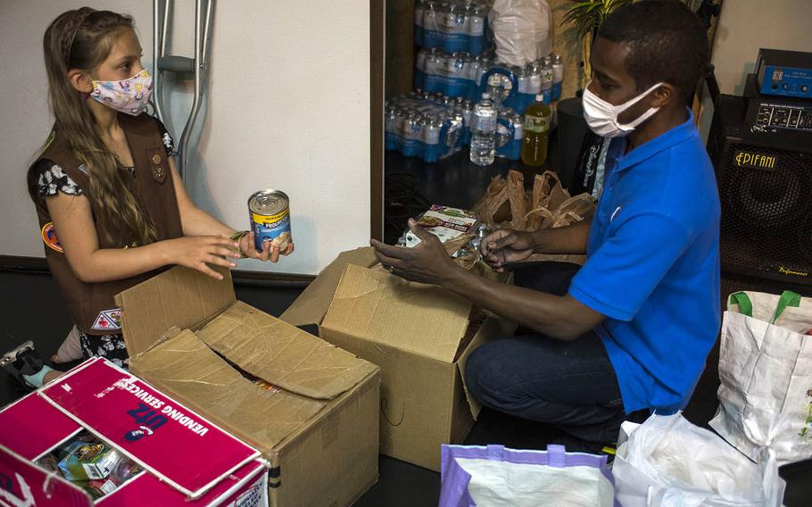 Girl Scout Eleanor Pierson, 9, of Yokota Air Base, Japan, helps Marcel Gadsden, pastor of the Japan Kingdom Builders Church in Fussa, sort hundreds of nonperishable food items she collected for the homeless, April 20, 2021.