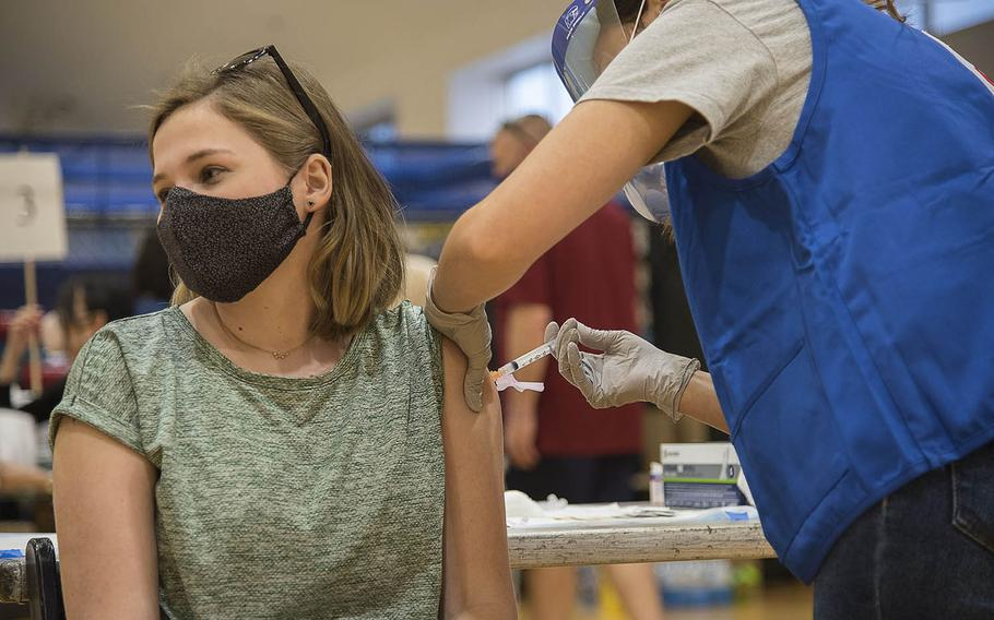 The daughter of a service member stationed at Yokota Air Base in western Tokyo receives the Moderna COVID-19 vaccine during a shot clinic at Yokosuka Naval Base, Japan, Wednesday, April 21, 2021.