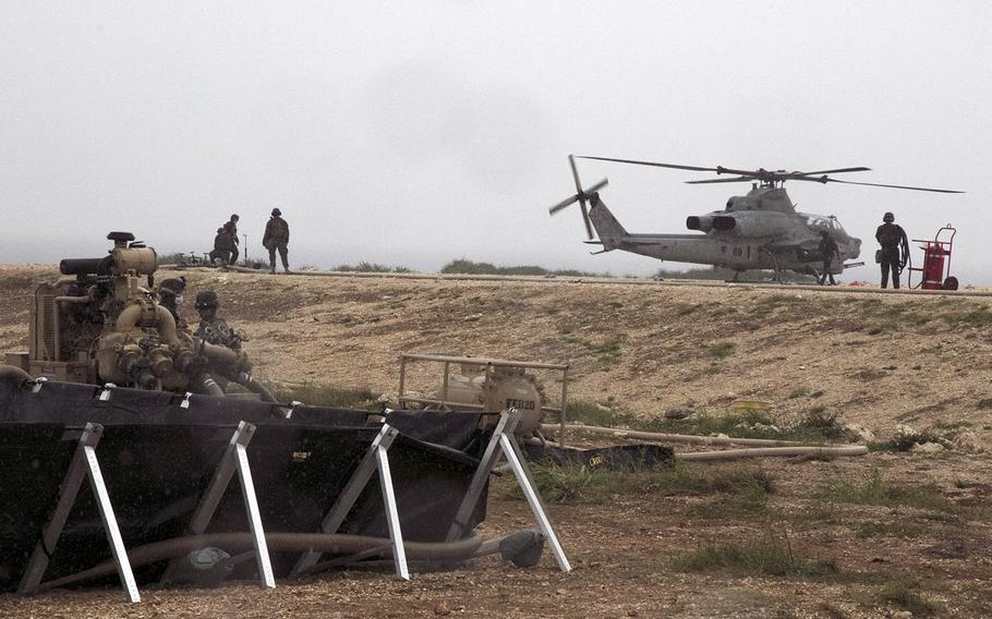 Members of Marine Wing Support Squadron 172 refuel an AH-1Z Viper attack helicopter on a makeshift landing pad on Ie Shima, Okinawa, April 16, 2021.