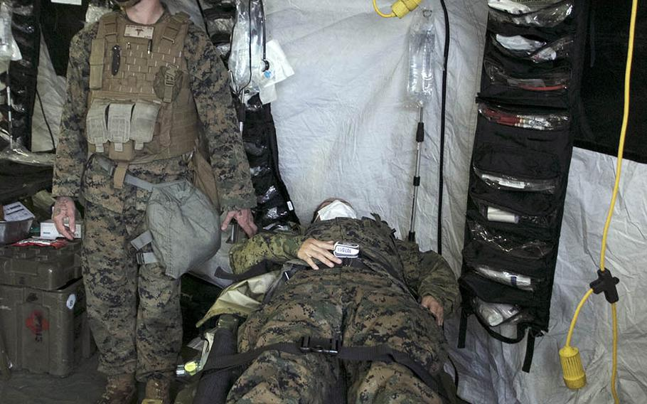 A mock casualty is brought into a medical tent during a 1st Marine Aircraft Wing combat readiness exercise on Ie Shima, Okinawa, April 16, 2021.