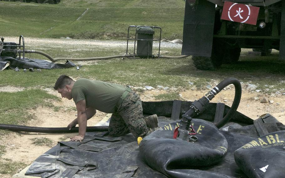A Marine from the 9th Engineer Support Battalion checks to make sure fuel is running to a 500-pound bladder during a combat readiness exercise for the 1st Marine Aircraft Wing at Kin Blue Beach, Okinawa, April 20, 2021.