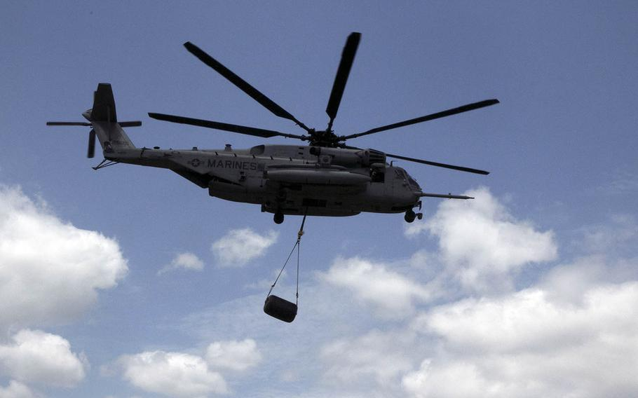 A CH-53 Sea Stallion from Marine Heavy Helicopter Squadron 465 carries a 500-pound fuel bladder off of Kin Blue Beach, Okinawa, during a combat readiness exercise, April 20, 2021.