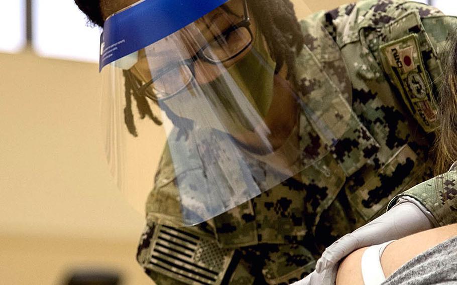 Navy Lt. Lachean Kimbrough delivers a dose of the Moderna coronavirus vaccine at Yokosuka Naval Base, Japan, April 21, 2021.