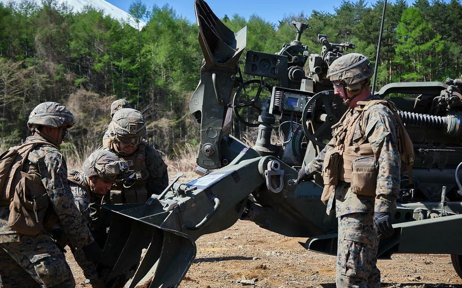 Members of 3rd Battalion, 12th Marine Regiment, 3rd Marine Division prepare to take an M777 A2 howitzer to a new firing position, during artillery relocation training at Camp Fuji, Japan, April 23, 2021.