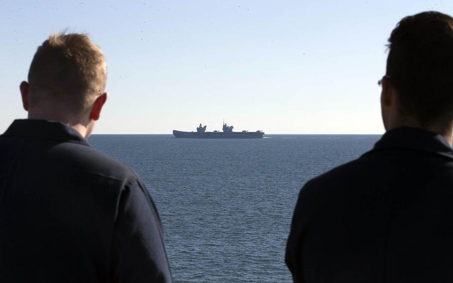 Sailors aboard the aircraft carrier USS Gerald R. Ford watch as the HMS Queen Elizabeth steams past in the Atlantic Ocean, Nov. 25, 2019.