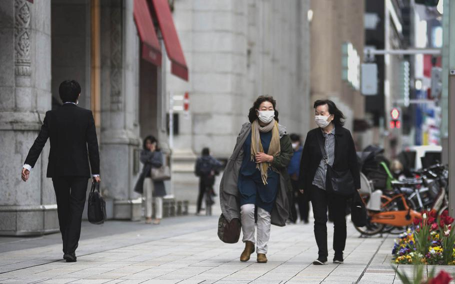 Pedestrians in central Tokyo wear face masks to prevent the spread of the coronavirus, April 6, 2021.