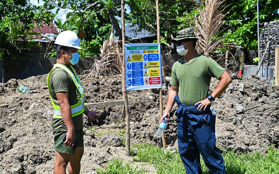 Philippine Army 1st Lt. Celestino Aporado Jr., left, and Marine Corps 1st Lt. Julian Taruc discuss the construction of a two-classroom building in Ilosong, Philippines, March 29, 2021.