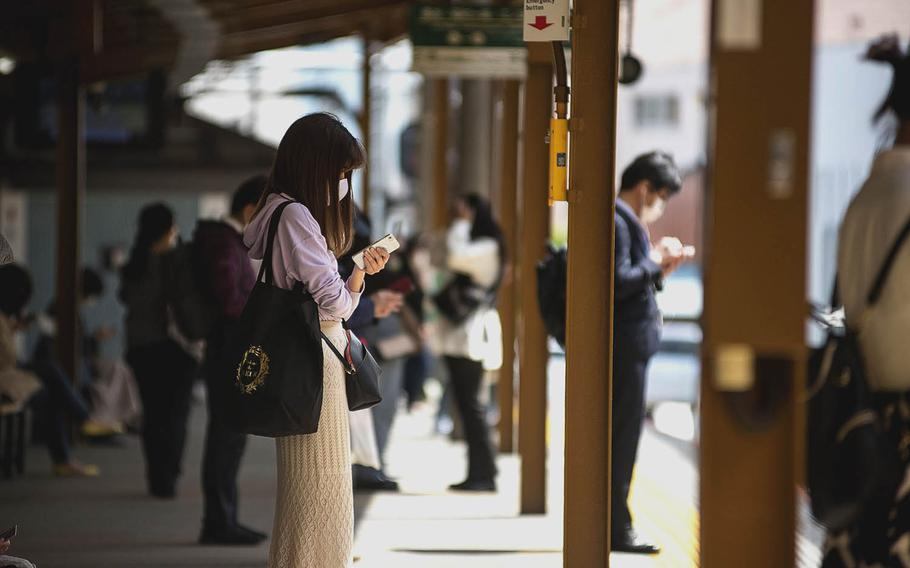 Travelers in coronavirus masks wait for their trains at Kamakura Station in Kanagawa prefecture, Japan, April 27, 2021.