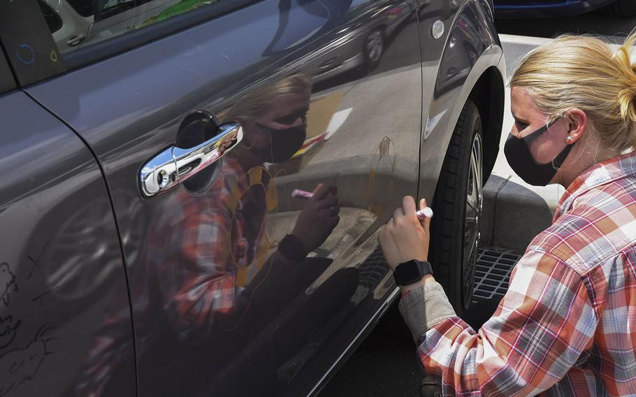 Yokota High School senior and future Coast Guard cadet Hannah Williams decorates her car for a Decision Day parade at the Air Force base in western Tokyo, Friday, April 30, 2021.