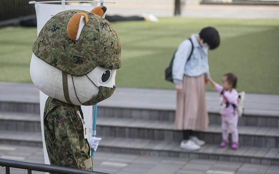 A mascot for the Japan Self-Defense Forces greets commuters outside Fujisawa Station in Kanagawa prefecture, Japan, April 27, 2021.