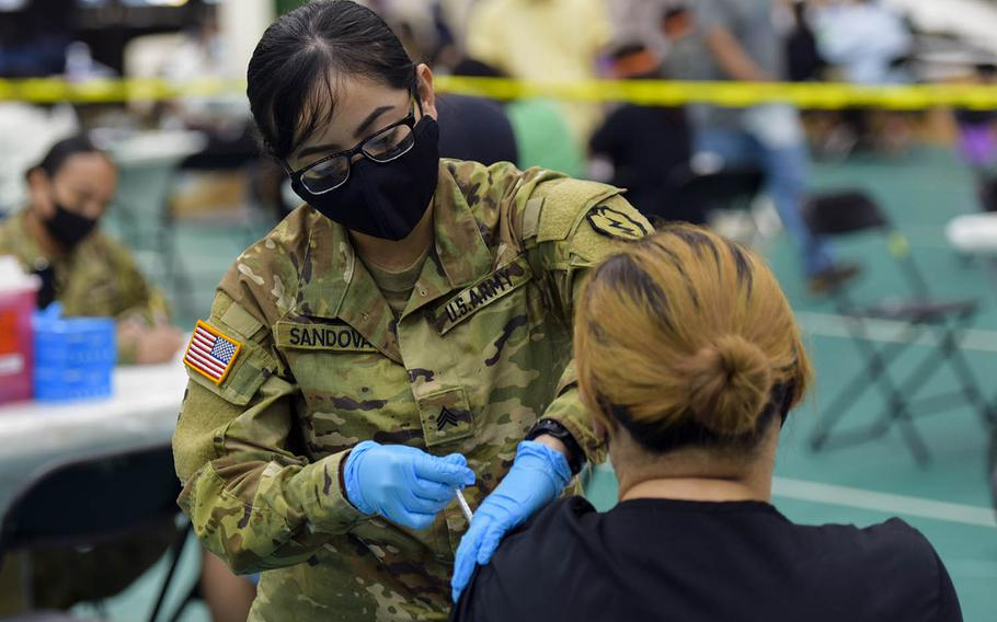 Army Sgt. Diana Sandoval, a combat medic specialist with the 25th Infantry Division, gives a COVID-19 vaccine during a community shot clinic at the University of Guam in Mangilao, April 16, 2021.