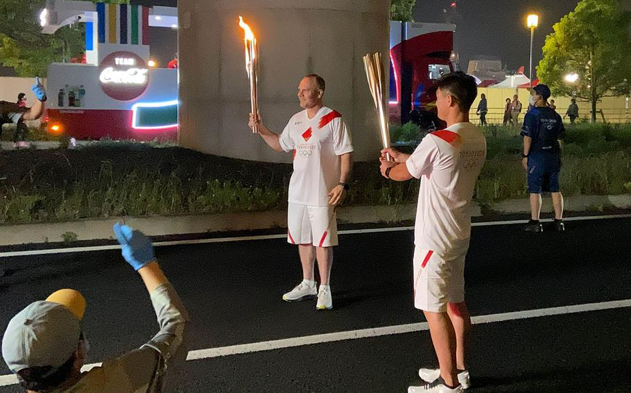 Capt. Brad Stallings, a former Sasebo Naval Base commander who now serves as the U.S. Naval Forces Japan chief of staff, carries the Olympic flame in Sasebo, Japan, Saturday, May 8, 2021.