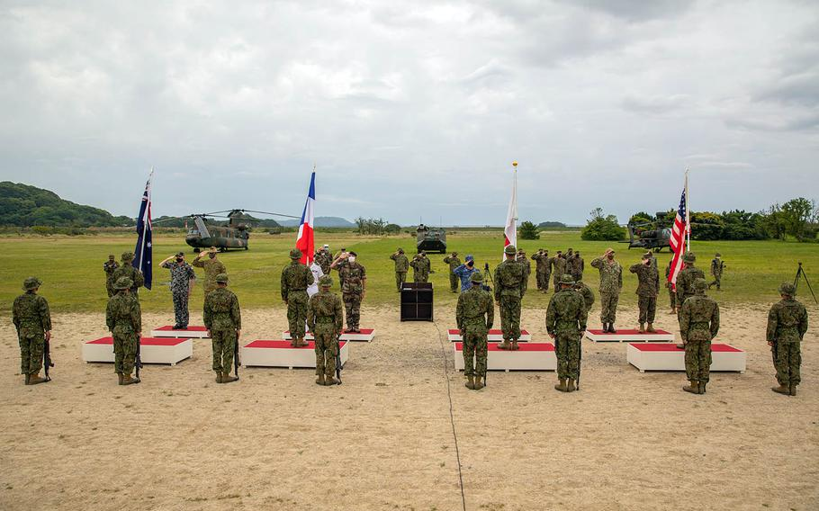 American, Japanese, French and Australian commanders salute their flags during the opening ceremony for exercise Jeanne D'Arc at Camp Ainoura in Sasebo, Japan, Tuesday, May 11, 2021.