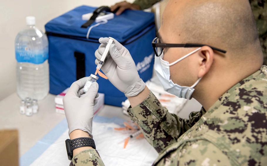 Petty Officer 2nd Class Jose Sabangan prepares a COVID-19 vaccine during a shot clinic at Naval Air Facility Atsugi, Japan, May 7, 2021.
