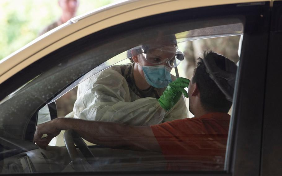 An airman from the 18th Medical Group at Kadena Air Base on Okinawa screens a driver for coronavirus in this undated photo posted to the base's official Facebook page Thursday, March 26, 2020.