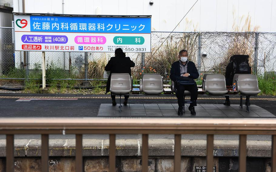Travelers wearing masks to ward off coronavirus in Fussa, a city within Tokyo, wait for trains at the city's main station on Friday, April 17, 2020.