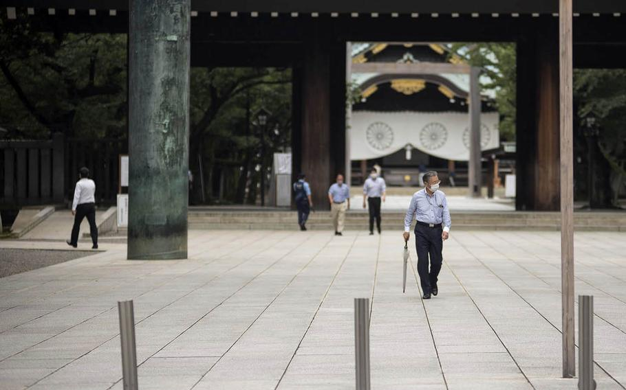 People wear masks as they stroll the grounds of Yasukuni Shrine in central Tokyo, Monday, July 27, 2020.