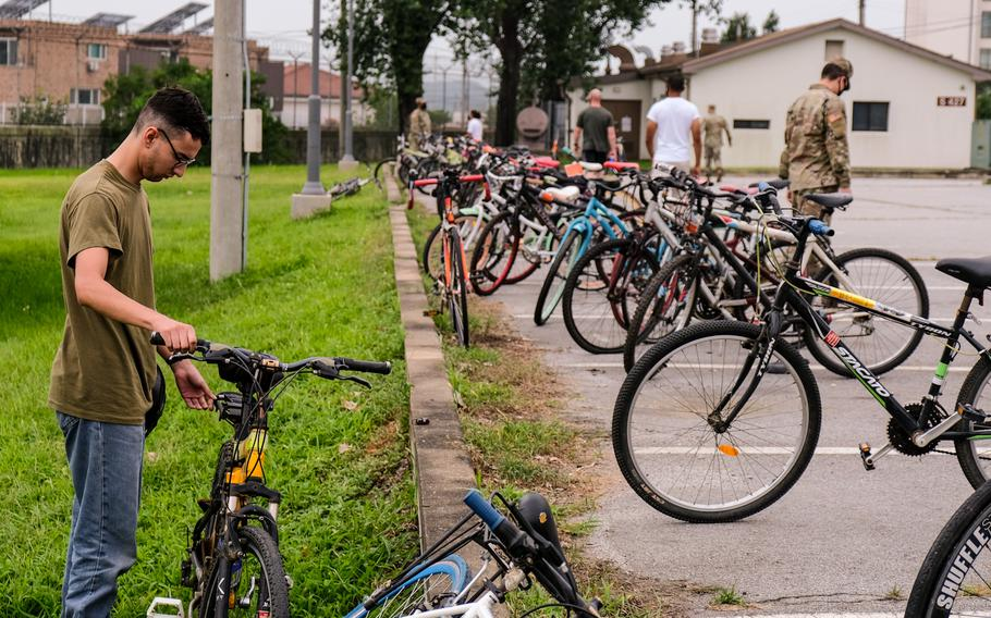 Pfc. Kevin Dunnaway, a videographer for Armed Forces Network-Korea, inspects one of the abandoned bicycles being given away at Camp Humphreys, South Korea, Saturday, Aug. 22, 2020.