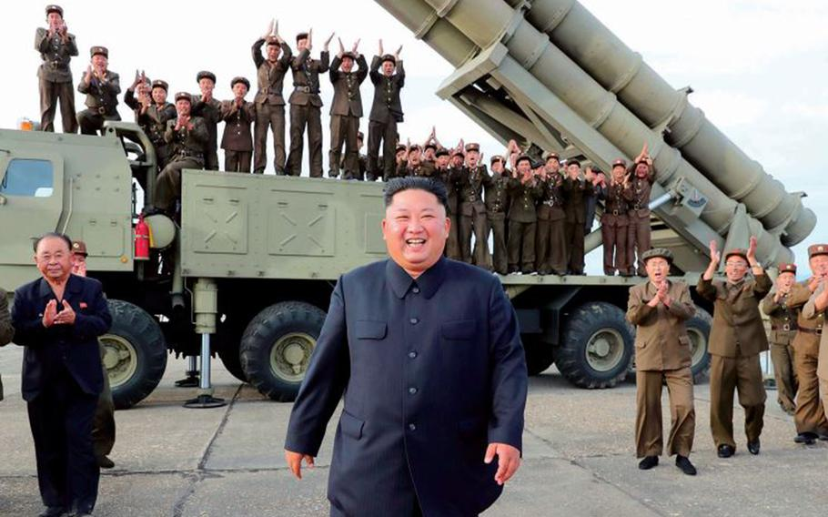 North Korean leader Kim Jong Un smiles in front of a missile launcher in this undated photo from the state-run Korean Central News Agency.