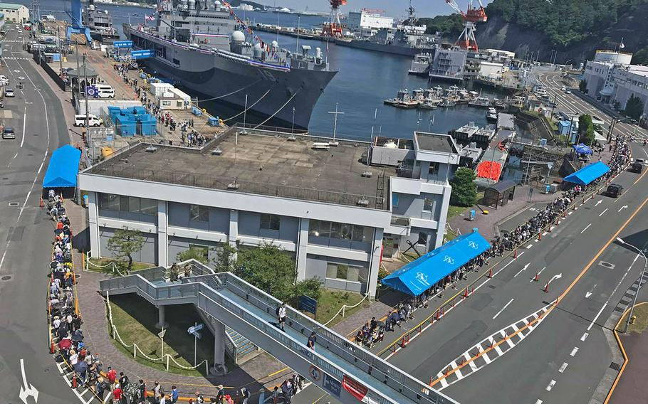Lines stretch around around the base pier to tour 7th Fleet flagship USS Blue Ridge during the 43rd annual Friendship Day at Yokosuka Naval Base, Japan, on Saturday, Aug. 3, 2019.