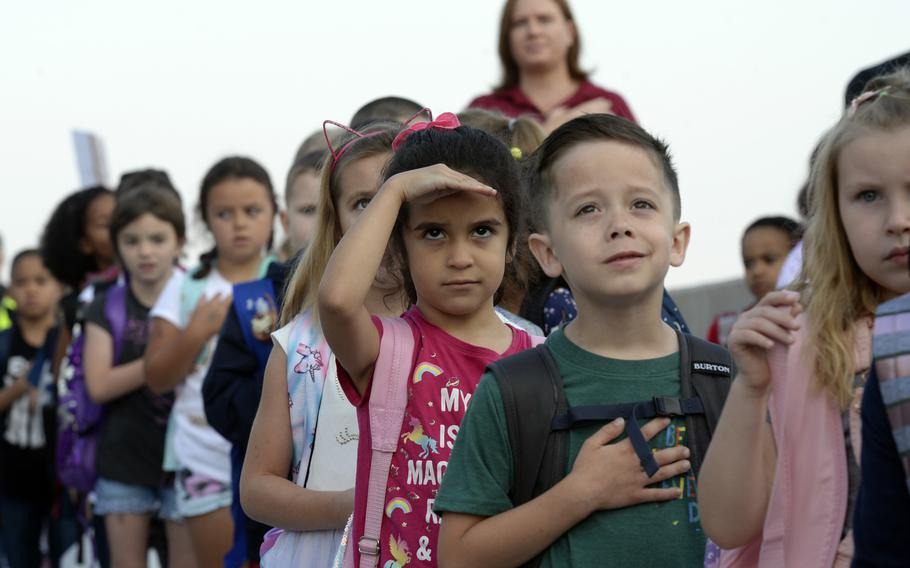 Students salute the flag during the national anthem on the first day of school at the new Vogelweh Elementary School, Monday, Aug. 26, 2019