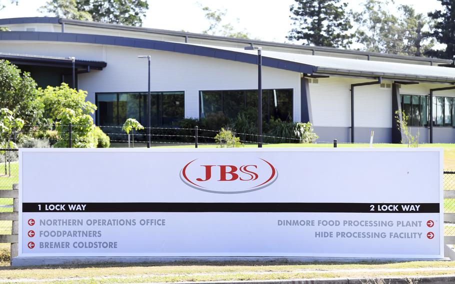 In this May 12, 2020, photo, the company logo sign sits at the entrance to the JBS Australia's Dinmore meatworks facility, west of Brisbane.